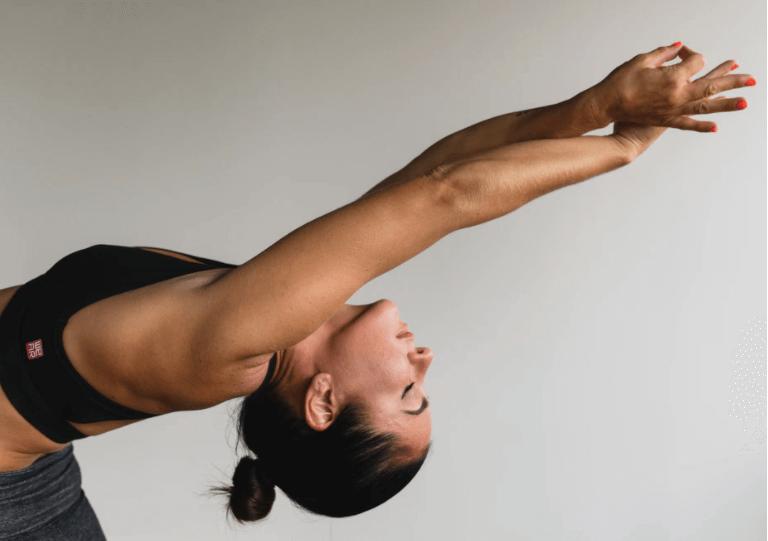 femme qui fait du yoga arpès une séance sur un tapis d'acupression